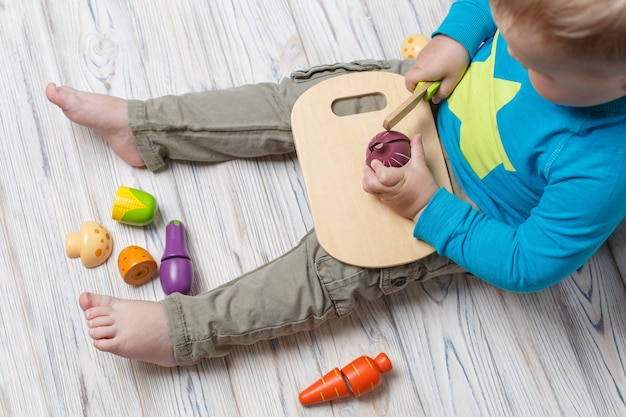 Niño juega en el chef de cerca. conjunto de verduras de madera de juguete