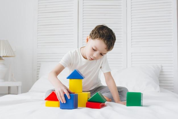 Niño juega y construye una torre de coloridos cubos de plástico.