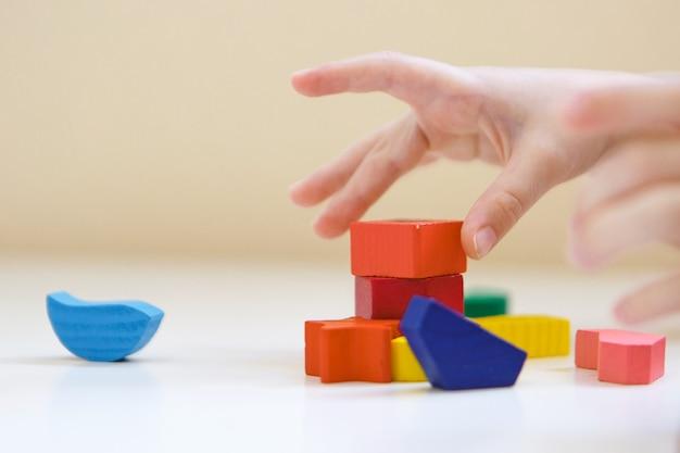 El niño juega con figuras de colores. detalles del juguete en las manos.