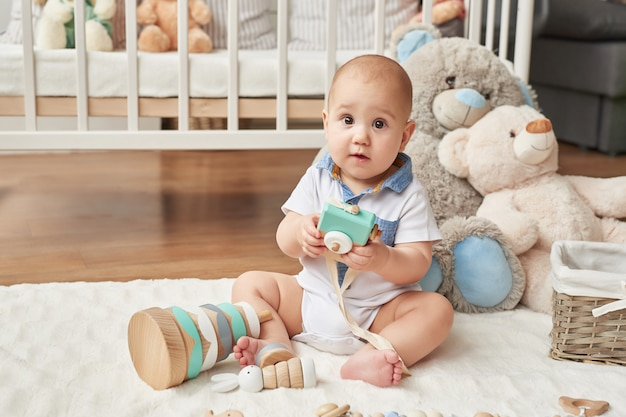 Niño juega juguetes de madera en una habitación infantil en colores brillantes, dormitorio infantil de estilo escandinavo