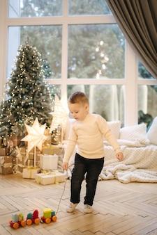 Niño juega con juguetes en vacaciones de navidad. niño lindo frente a una ventana grande. árbol de navidad