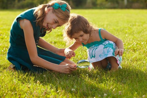 Niño juega con lupa en el jardín.
