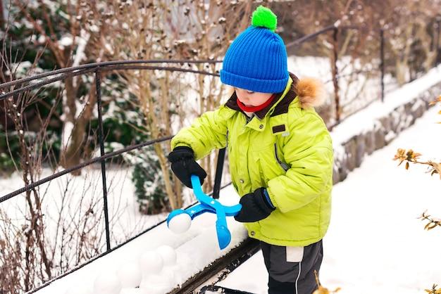 Niño juega con nieve al aire libre