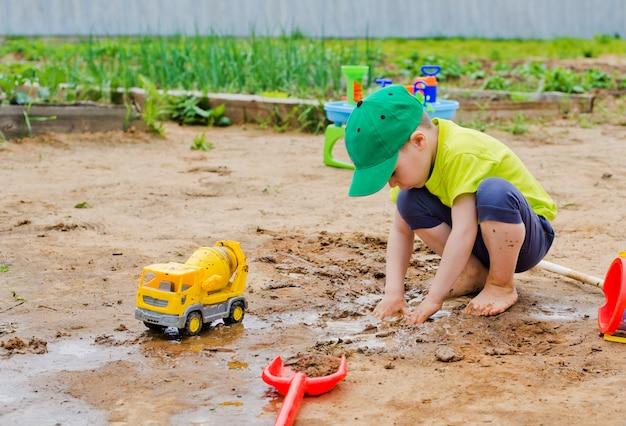El niño juega en el verano en el barro.