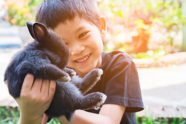 Niño jugando adorable conejo bebé