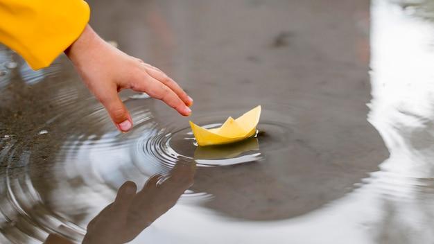 Niño jugando en el agua con un primer plano de barco de papel