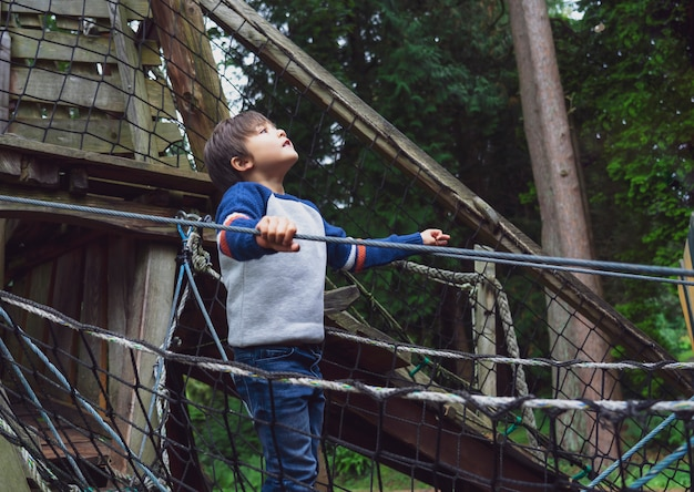 Niño jugando al aire libre en un parque de aventuras