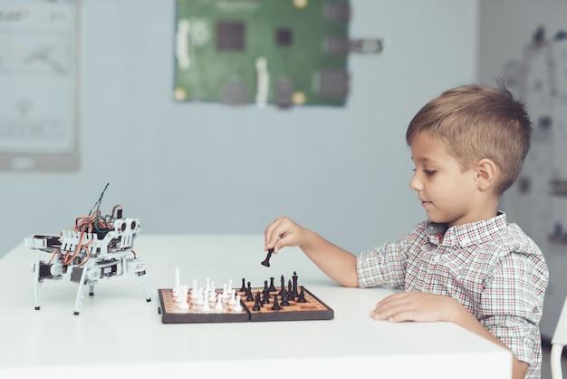 Niño jugando al ajedrez con un pequeño robot en la mesa.