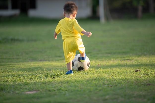 Niño jugando al fútbol en el campo.