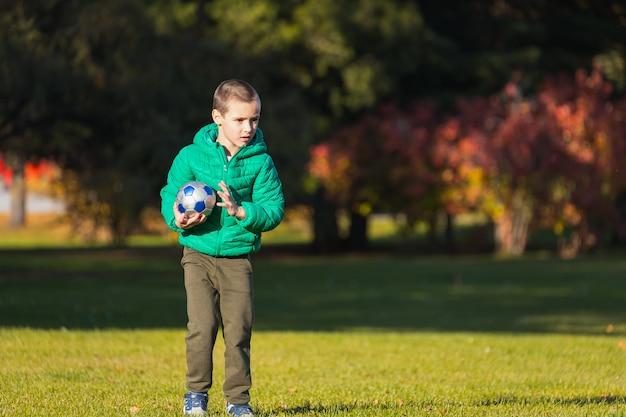Niño jugando al fútbol con el fútbol en el campo en el parque otoño