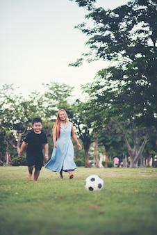 Niño jugando al fútbol soccer con la madre en el parque