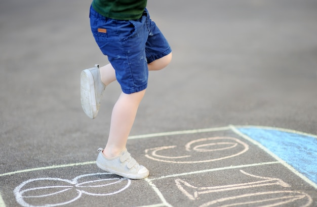 Niño jugando al juego de rayuela en el patio al aire libre en un día soleado