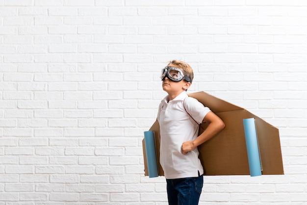 Niño jugando con alas de avión de cartón posando con los brazos en la cadera