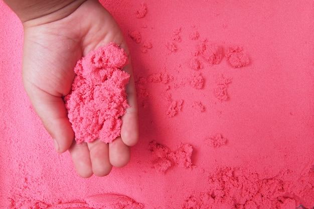 Un niño jugando arena roja. textura de fondo