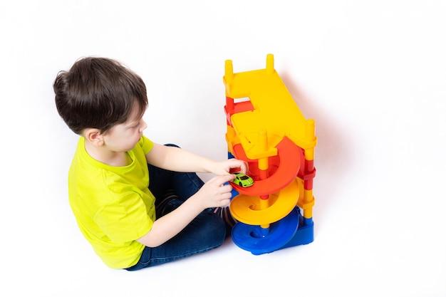 Niño jugando con autos en el estacionamiento. juguete para niños. un niño juega con juguetes en una pared blanca. estacionamiento luminoso para autos. infancia feliz