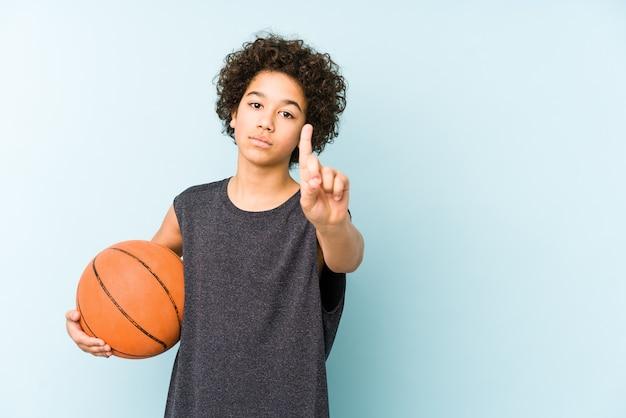 Niño jugando baloncesto aislado sobre fondo azul que muestra el número uno con el dedo.