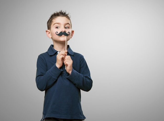 Niño jugando con un bigote falso