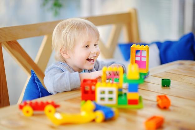 Niño jugando con bloques de plástico de colores en el jardín de infantes o en casa