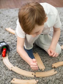 Niño jugando con caminos de madera y juego de autos en el piso