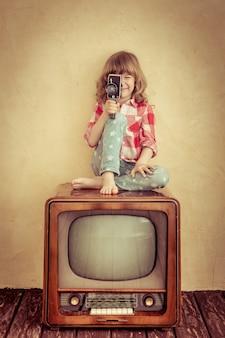Niño jugando en casa. niño haciendo una película con cámara retro. concepto de cine