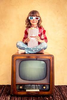 Niño jugando en casa. niño sentado en la televisión retro y comiendo palomitas de maíz. concepto de cine