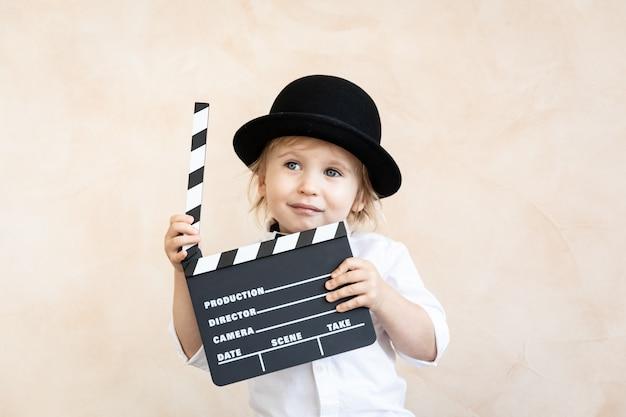 Niño jugando en casa. niño sosteniendo el tablero de la chapaleta. concepto de cine retro