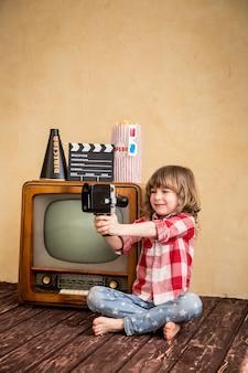 Niño jugando en casa. niño tomando selfie con cámara retro. concepto de cine