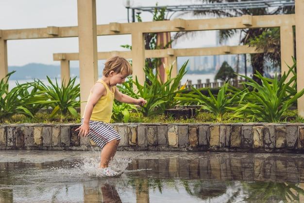 Niño jugando en un charco