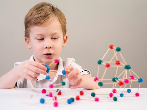 Niño jugando con colorido juego de átomos en casa