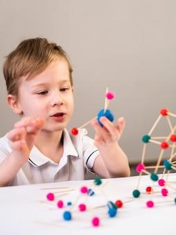 Niño jugando con colorido juego de átomos en el interior