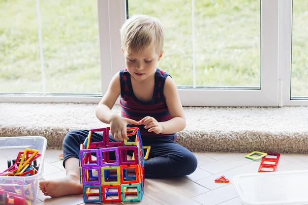 El niño está jugando con un constructor magnético multicolor, construyendo una torre. juguetes educativos. un elemento fundamental para un bebé o un niño pequeño desorden en la sala de juegos