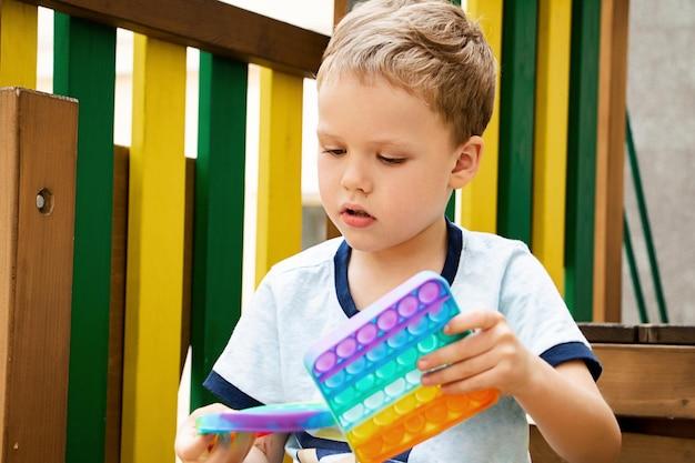 Niño jugando con dos nuevos juguetes de silicona póngalo en el patio de recreo