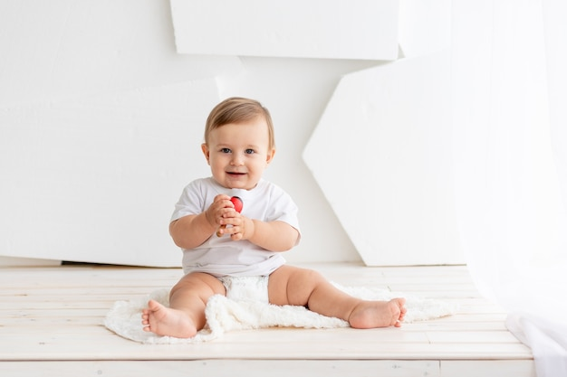 El niño está jugando, feliz y lindo bebé de seis meses de edad con una camiseta blanca y pañales se sienta sobre un fondo claro en casa y juega, lugar para el texto