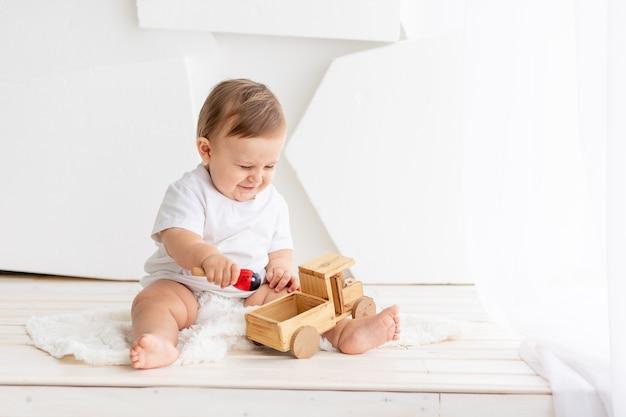 El niño está jugando, feliz y lindo bebé de seis meses de edad con una camiseta blanca y pañales se sienta sobre un fondo claro en casa y juega con una máquina de escribir de madera, espacio para texto