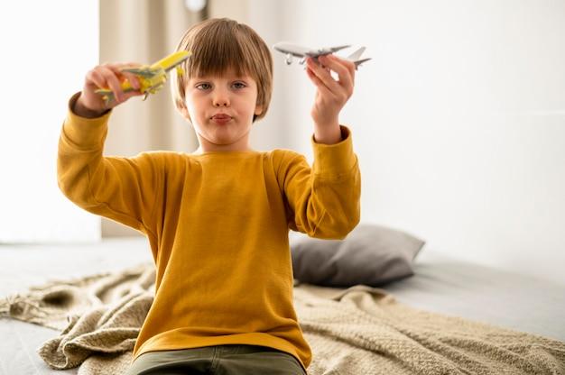 Niño jugando con figuritas de avión en casa