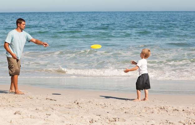 Niño jugando frisbee con su padre