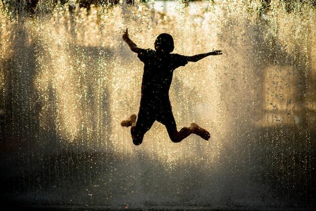 Niño jugando a la fuente de gotas de agua debajo de la tela y el paraguas
