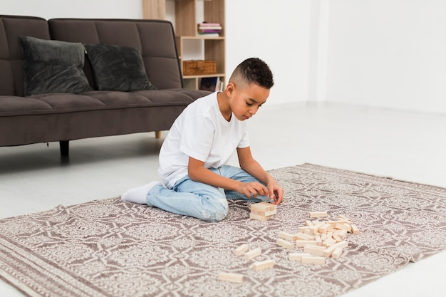 Niño jugando un juego de torre de madera en casa