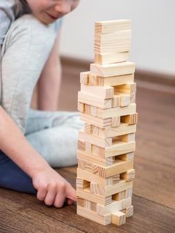 Niño jugando con juego de torre de madera en el piso