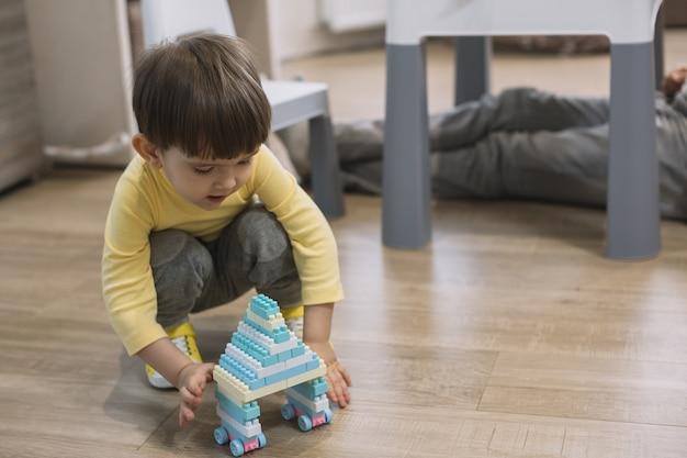 Niño jugando con juguete y padre piernas borrosas