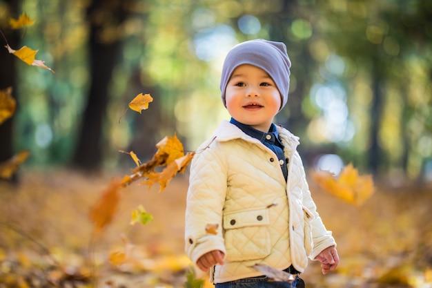 Niño jugando y lanzando hojas en el parque otoño