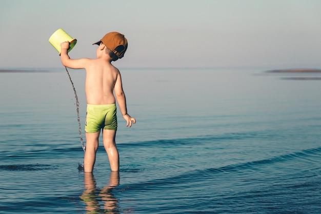 Niño jugando en el mar con agua y un balde.