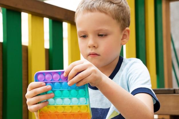 Niño jugando con el nuevo juguete de silicona pop itnuevo juguete sensorial antiestrés para niños y adultos