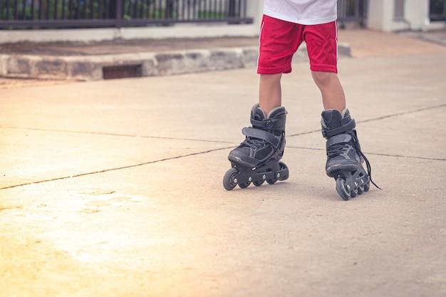 Niño jugando patinar en la carretera de cemento
