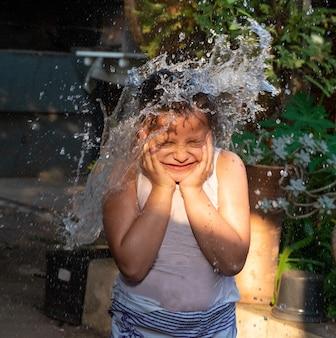 Niño jugando en el patio con agua en el verano brasileño