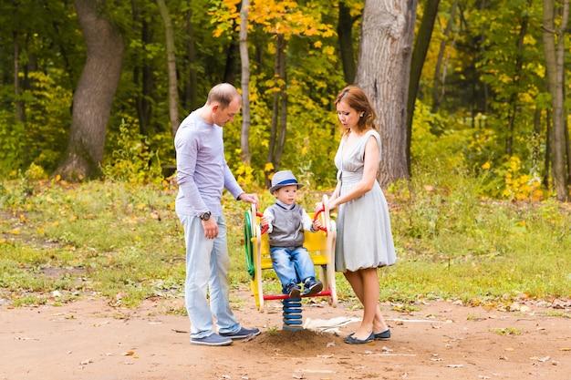 Niño jugando en el patio de recreo con madre y padre