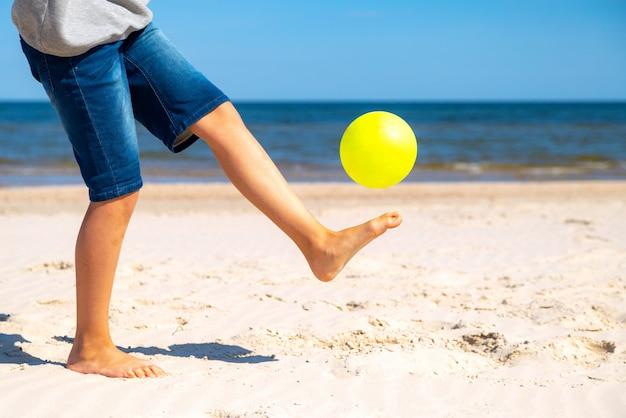 Niño jugando con pelota de playa amarilla en la arena junto al agua de mar en un día soleado.