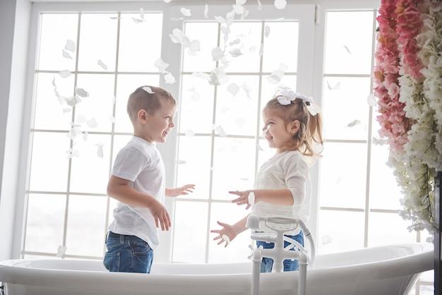 Niño jugando con pétalos de huevas en casa baño. niña y niño fawing diversión y alegría juntos. infancia y realización de sueños, fantasía, imaginación