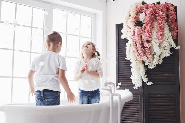 Niño jugando con pétalos de rosa en el baño de su casa. niña y niño fawing diversión y alegría juntos. infancia y realización de sueños, fantasía, imaginación