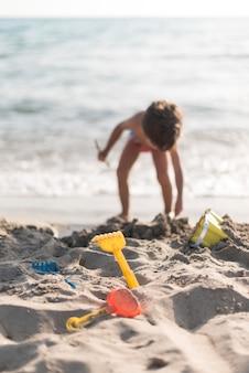 Niño jugando en la playa con juguetes.